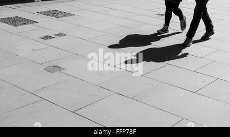 Shadows of two walking pedestrians projected on the sidewalk. Black and white. - Stock Photo