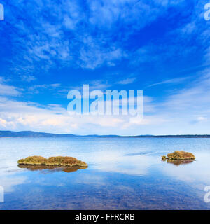 Two small green island in a blue lake under clear sky. Orbtello lagoon, Tuscany, Monte Argentario, Italy. - Stock Photo