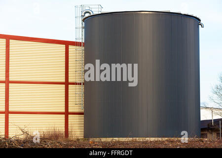 Large black silo or storage building with an aluminum or steel ladder on the outside. Red and yellow building behind - Stock Photo