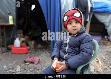 Portrait of a refugee boy (5 years) from Syria eating an apple, now lives with his parents in a tent camp near Calais, - Stock Photo