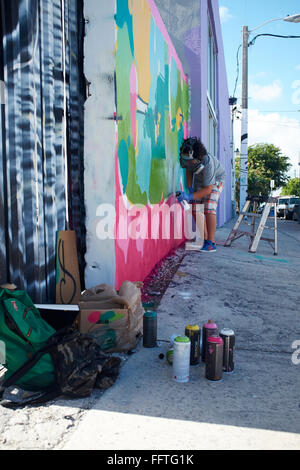 Graffiti sprayer in Miami for Art Basel 2014. In the foreground the spray cans. - Stock Photo