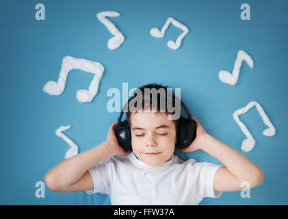 boy on blue blanket background with headphones - Stock Photo