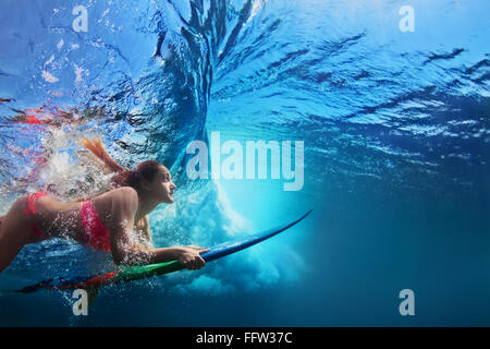 Young girl in bikini - surfer with surf board dive underwater under big ocean wave. - Stock Photo