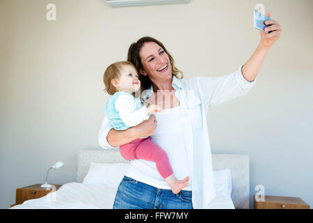 Smiling woman taking a selfie with her baby - Stock Photo