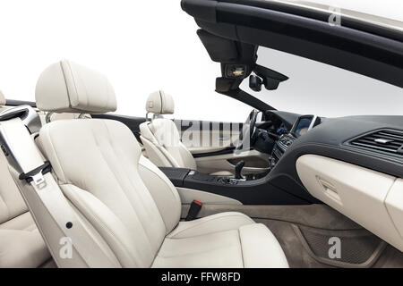 Car interior luxury white seats with black dashboard. Comfortable cabriolet salon. Cleaning and detailing car service. - Stock Photo
