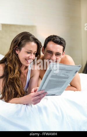 Smiling couple lying in bed - Stock Photo
