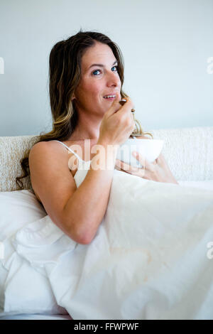 smiling woman eating a bowl of cereal - Stock Photo