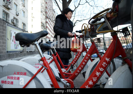Beijing, China. 17th Feb, 2016. A resident returns a public bike at a service site in Chaoyang District in Beijing, - Stock Photo