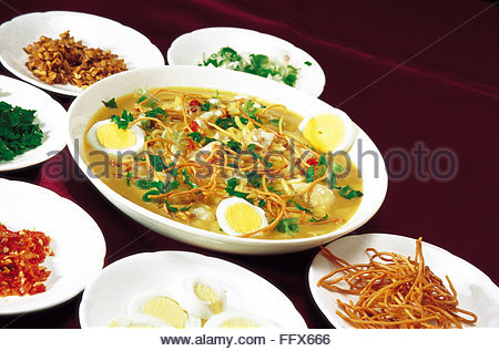Non vegetarian meal Malaysian Burmese cuisine fish curry noodles boiled eggs slices served dish violet background - Stock Photo