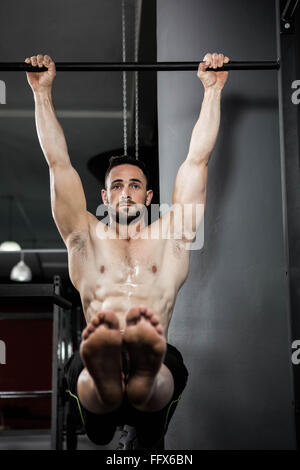 Shirtless man doing pull up - Stock Photo