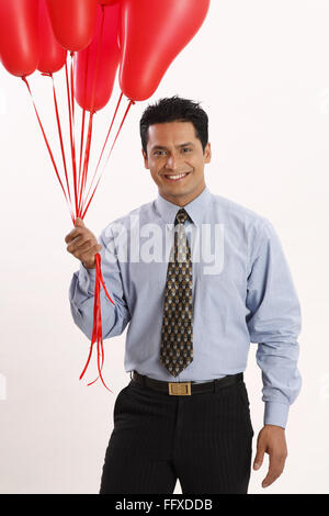Businessman holding red coloured gas balloons in one hand MR#703T - Stock Photo