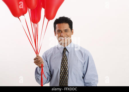 Businessman holding red color gas balloons in one hand MR#703T - Stock Photo