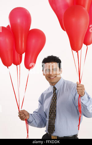 Businessman holding red color gas balloons in both hands MR#703T - Stock Photo