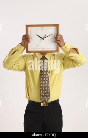 Businessman holding wall clock in both hands over his face and hiding it MR#703T - Stock Photo