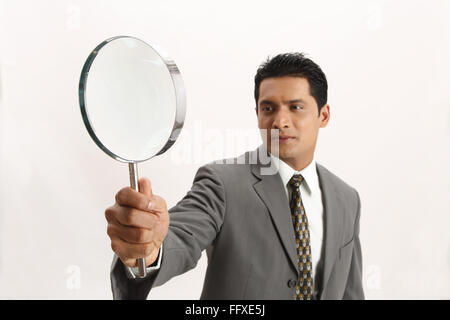 Businessman holding magnifying glass in right hand MR#703T - Stock Photo