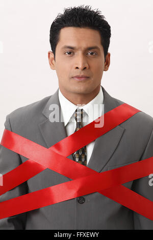 Businessman tied with red ribbon - Model Release # 703T - Stock Photo