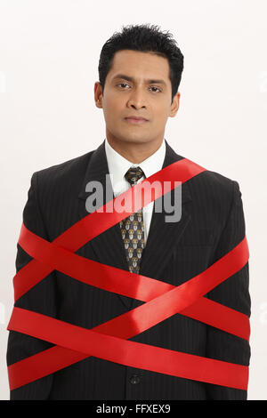 Businessman tied with red ribbon MR#703T - Stock Photo