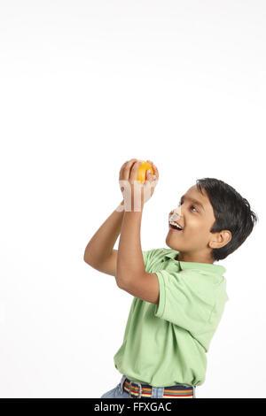 Ten year old boy taken catch of orange in both hands MR#703V - Stock Photo