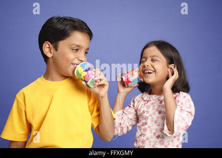 Ten and eight year old boy and girl speaking on child's telephone made of two glasses and wire MR#703U,703V - Stock Photo