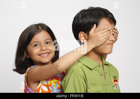 Eight year old girl closed ten year old boy's eyes from behind MR# 703U,703V - Stock Photo