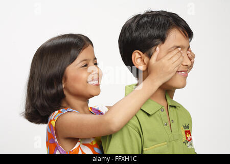 Eight year old girl closed ten year old boy's eyes from behind MR# 703 U,703 V - Stock Photo