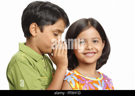 Ten year old boy whispering something in eight year old girl's ear MR# 703U,703V - Stock Photo
