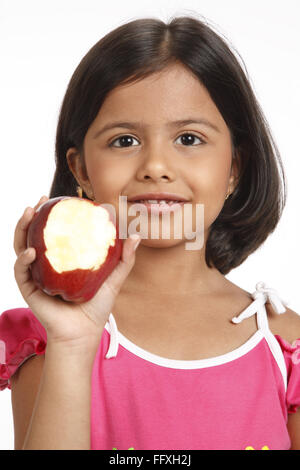 Eight year old girl showing half eaten apple by holding in her right hand near her face MR#703U - Stock Photo
