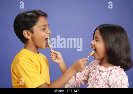 Ten and eight year old boy and girl feeding lollipops to each other MR#703U,703V - Stock Photo