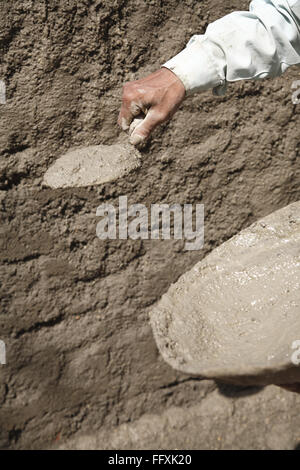 Mason using patter and trowel for plastering mixture of cement on wall - Stock Photo