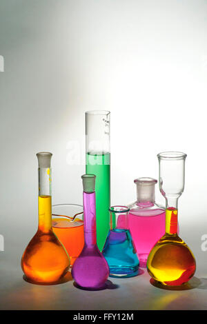 Concept , various colourful chemicals in beakers on white background - Stock Photo