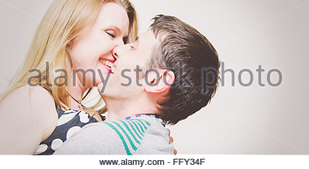 Cheerful Young Couple Embracing Against White Background - Stock Photo