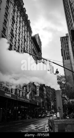 Smoke Emitting From Chimney By Street Against Buildings - Stock Photo