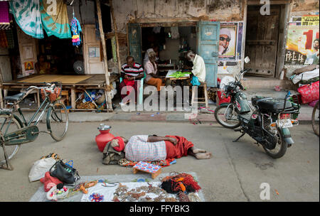 Street scene with sleeping roadside trader and shop keepers in Madurai, Tamil Nadu, India, Asia - Stock Photo