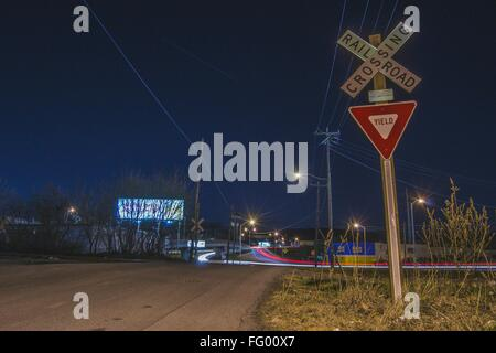 Light Trails On Road By Railroad Crossing Sign Against Clear Sky At Night - Stock Photo