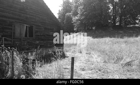 Barbed Wire Fence In Front Of Field With Old Barn - Stock Photo