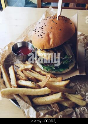 Burger And French Fries Served On Table - Stock Photo