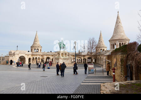 BUDAPEST, HUNGARY - FEBRUARY 02: Tourists walking around Fisherman's Bastion, with bronze statue of Saint Stephen - Stock Photo
