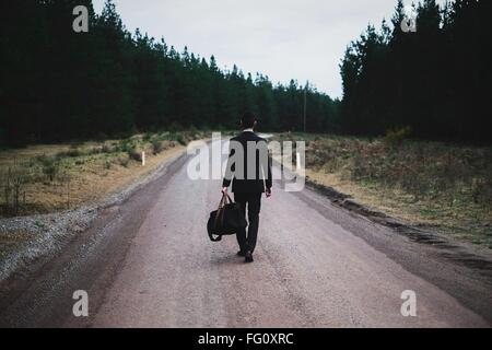 Full Length Rear View Of Man With Luggage Walking On Road Against Sky - Stock Photo