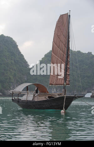 A single sailed junk moored in a fishing village in Halong Bay, North Vietnam - Stock Photo