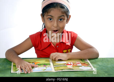 South Asian Indian six years old girl reading comic book MR#364 - Stock Photo
