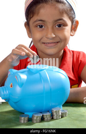 South Asian Indian six years old girl saving coins in piggy bank MR#364 - Stock Photo