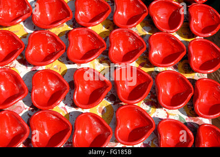 Red oil lamps made of mud drying - Stock Photo