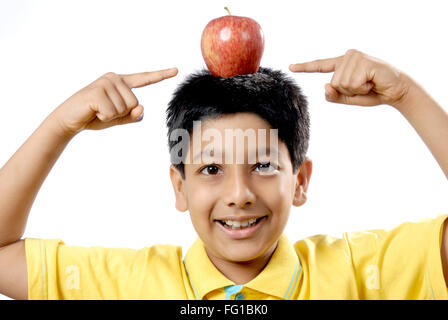 Young boy balancing apple on head and showing with fingers MR#152 - Stock Photo