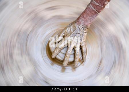 Pottery , artist muddy hands making clay pot giving shape on spinning wheel , semi urban village Dilwara , Udaipur - Stock Photo