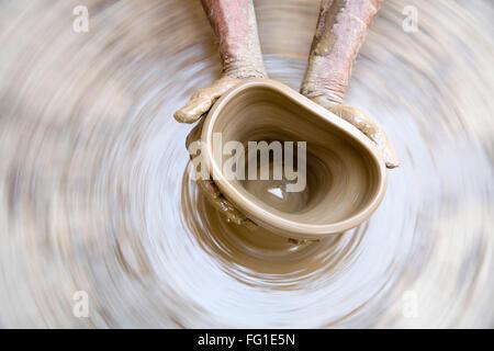 Pottery , artist muddy hands making clay pot giving shape on spinning wheel , semi urban village Dilwara Udaipur - Stock Photo