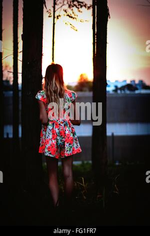 Rear View Of Girl Wearing Floral Dress Standing By Tree - Stock Photo