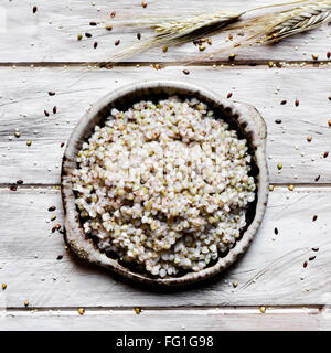 high-angle shot of an earthenware bowl with cooked buckwheat seeds on a rustic wooden table - Stock Photo