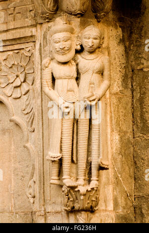 Muslim man and woman couple carved in stone on wall of Maheshwar temple , Maheshwar , Madhya Pradesh , India - Stock Photo