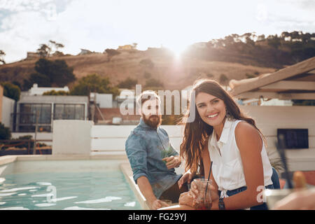 Portrait of young woman sitting by pool with friends having a party in evening. She is smiling and looking away. - Stock Photo