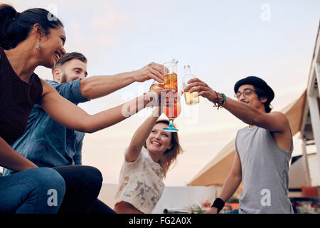 Portrait of young people toasting cocktails during a party. Four young friends enjoying in a party. Young man and - Stock Photo